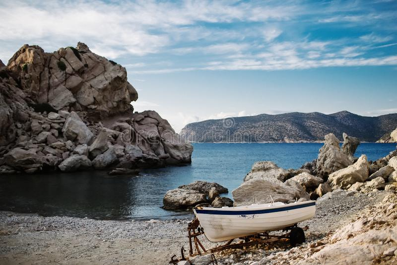 Panorama with a beautiful bay, stone beach and clear blue water. Boat on the bay on Rhodes island, Dodecanese, Greece royalty free stock photography