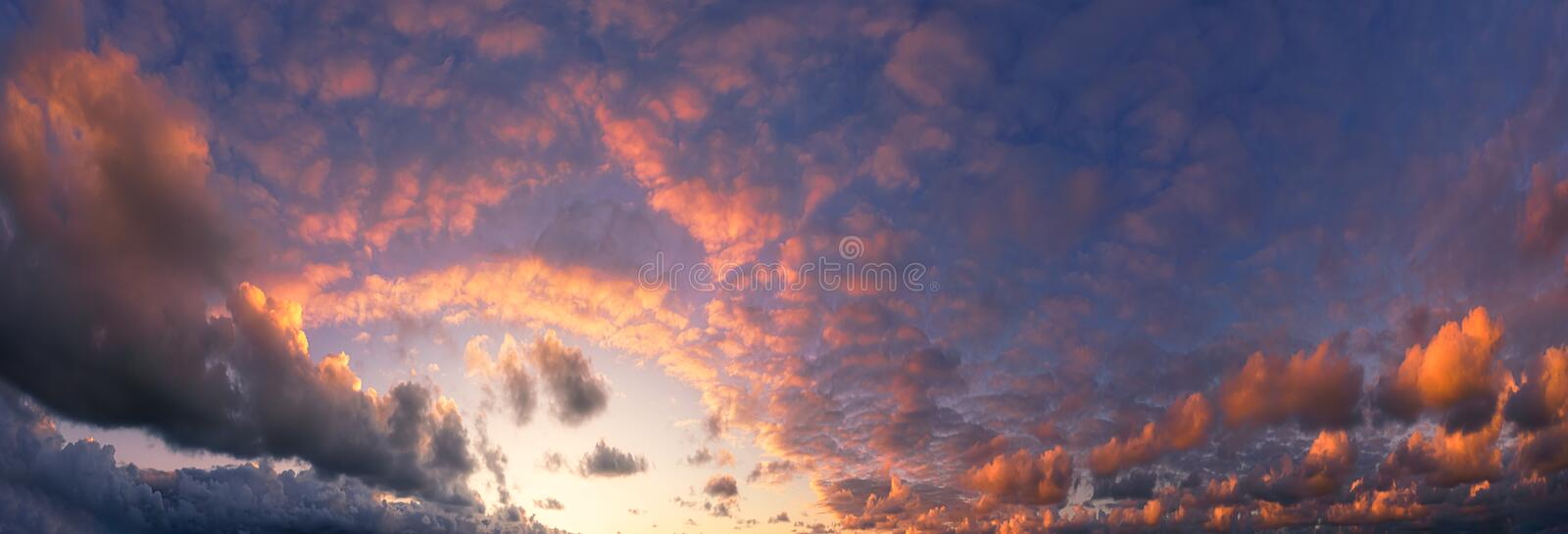 Panorama of beautiful cloudscape with red clouds. At sunset stock image
