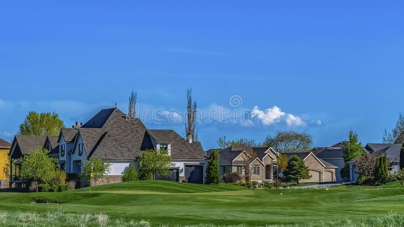 Panorama Beautiful houses surrounded by lush trees and vast grassy terrain. Vibrant blue sky with clouds can be seen over the landscape on this sunny day stock photo