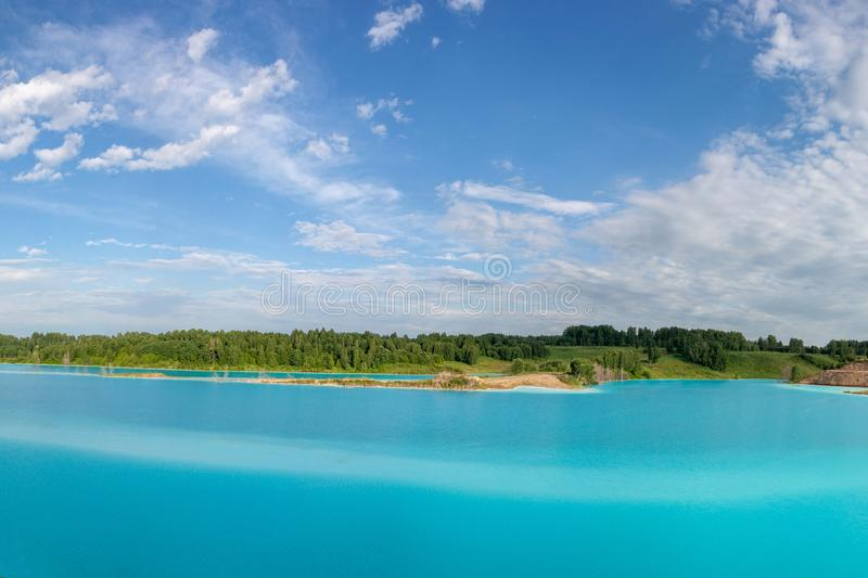 Panorama of a beautiful lake with azure-blue water. Green trees, blue sky. Summer s royalty free stock photography