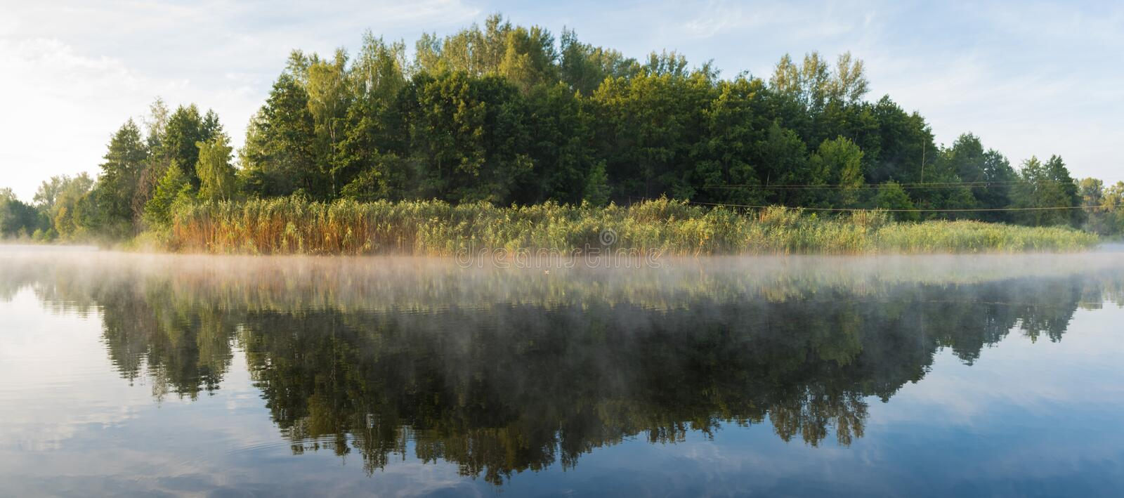 Panorama. Beautiful landscape. Dawn on the river with foggy haze on a background of green forest.  stock photography