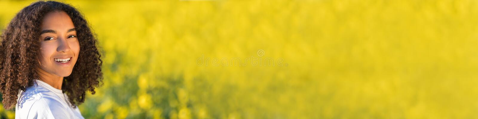 Happy Mixed Race African American Teenager Woman in Yellow Flowers. Panorama beautiful mixed race biracial African American girl teenager female young woman royalty free stock photography