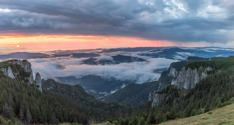 Panorama of a beautiful mountain view with fog over the peaks at sunrise stock image