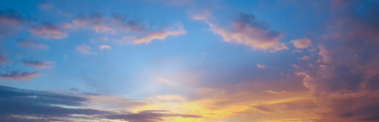 Panorama of Beautiful skyscape clear blue sky and golden cloud background during sunset. Clearing day and Good weather in the stock photo
