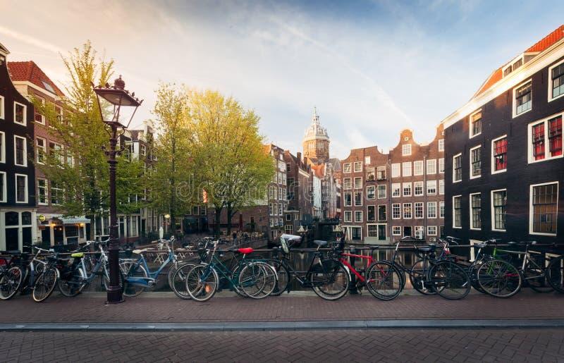 Panorama of beautifull Amsterdam bridge with bicycles, Holland. Panorama of beautifull Amsterdam bridge with bicycles and typical dutch houses at sunset, Holland stock photos
