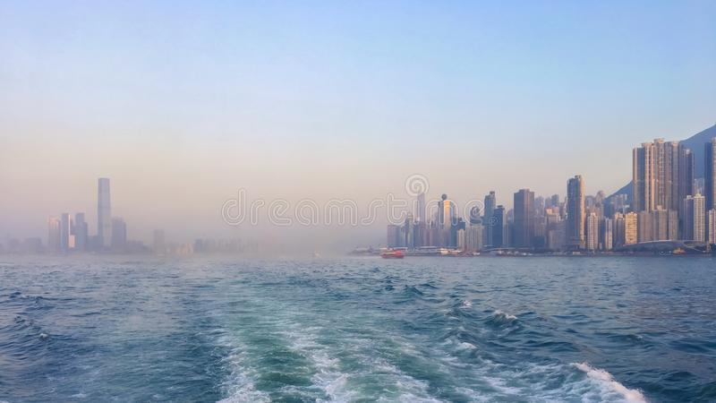 Panorama of the big Asian megalopolis at sunset in a haze, a view of the big city about ship boards, skyscrapers against the backg. Megalopolis panorama in royalty free stock photography