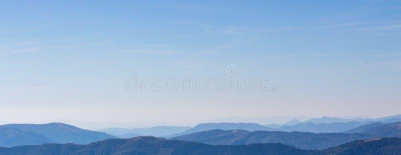 Panorama blu dei picchi di montagne Concetto di calma e di vastità Chiaro cielo blu sopra le montagne blu sul tramonto fotografia stock