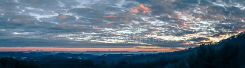 Panorama blu della cresta delle montagne fumose al tramonto fotografie stock