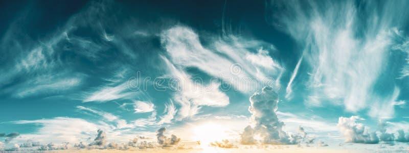 Panorama of blue cloudy sky and rising sun royalty free stock photos