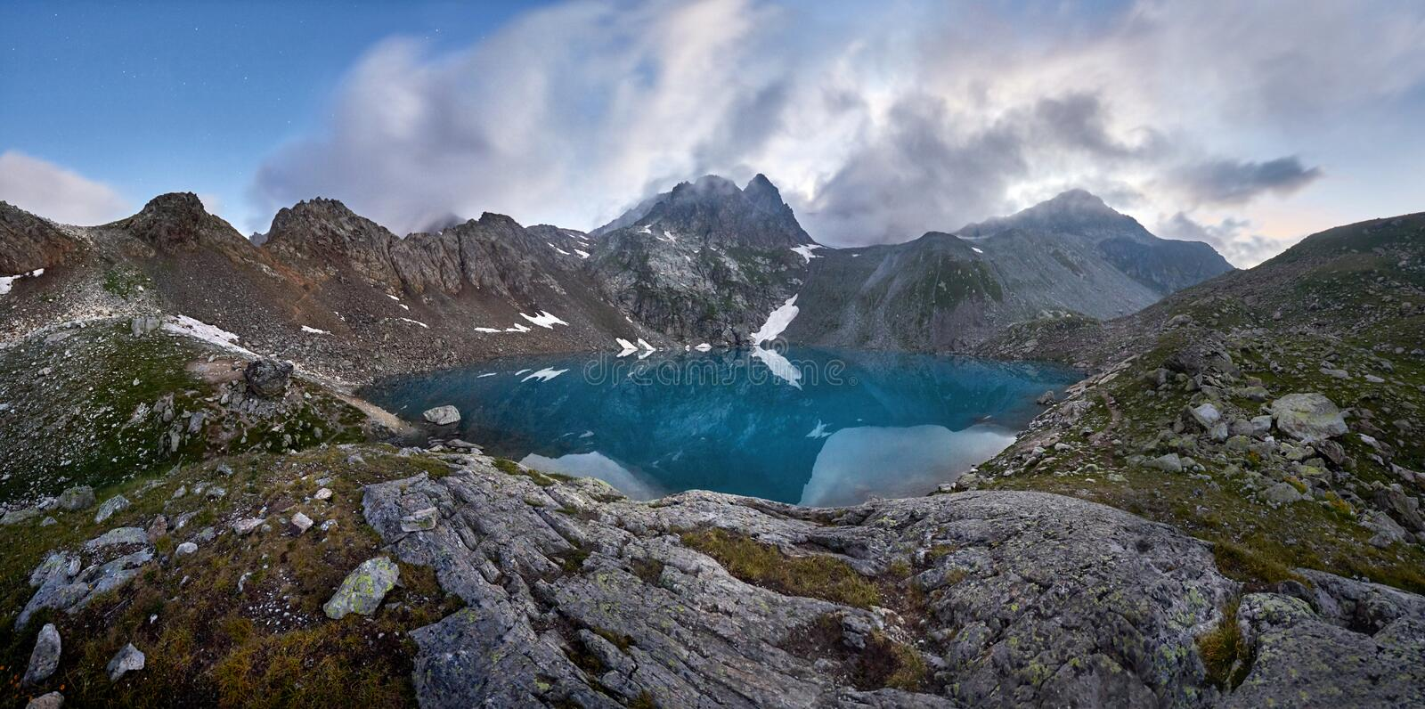Panorama of Blue mountain lake high in the mountains. Untouched. Wilderness, no one around. Turquoise lake and the melting glaciers stock photos