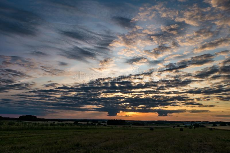 Panorama of blue red sky background with evening fluffy curly rolling clouds with setting sun. Good windy weather.  royalty free stock images