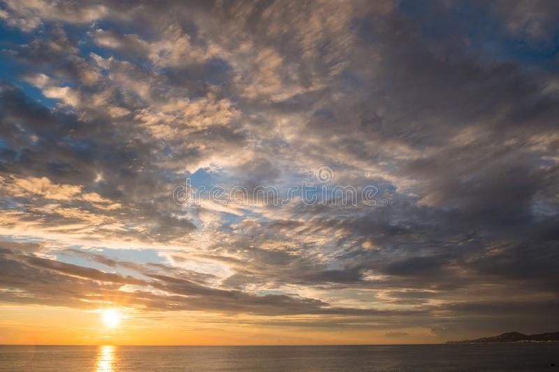 Panorama blue sky with a cloud texture and setting sun over the sea royalty free stock photo
