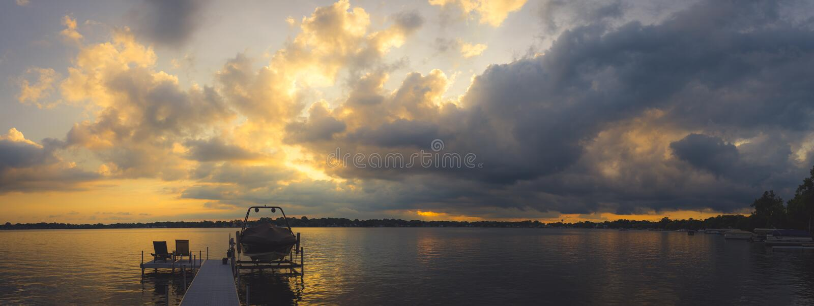 Panorama of boats docked with the sun setting. In the lake royalty free stock image