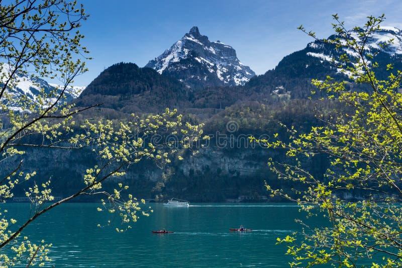 Panorama bonito do lago da montanha de turquesa com picos cobertos de neve e prados e florestas e barcos verdes no lago foto de stock