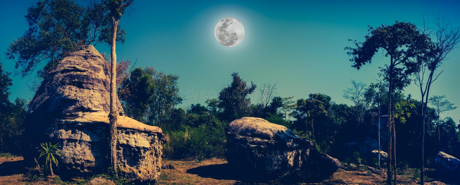 Panorama of boulders against beautiful sky and full moon over tr stock image