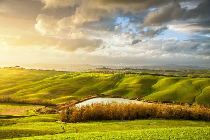Panorama brumeux de la Toscane au coucher du soleil, Rolling Hills, lac, champs, m photographie stock libre de droits