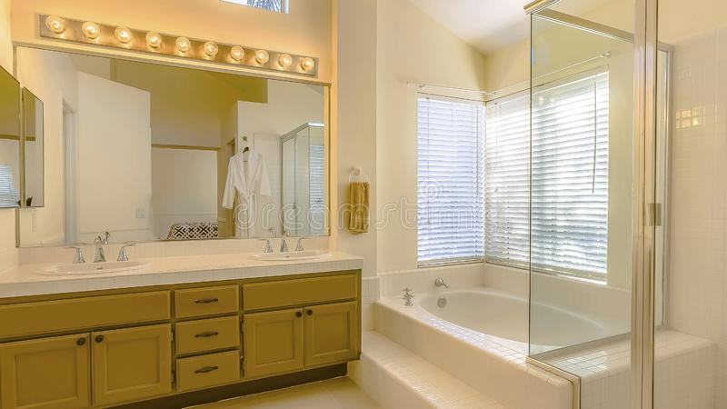 Panorama Built in bathtub and shower with glass door inside a beautiful bathroom. Vanity unit with double sink, large mirror, bright lights, and wood cabinets royalty free stock photos