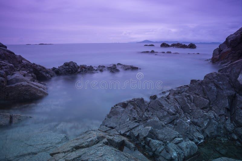 Panorama - côte au coucher du soleil/à aube et aux roches photos stock