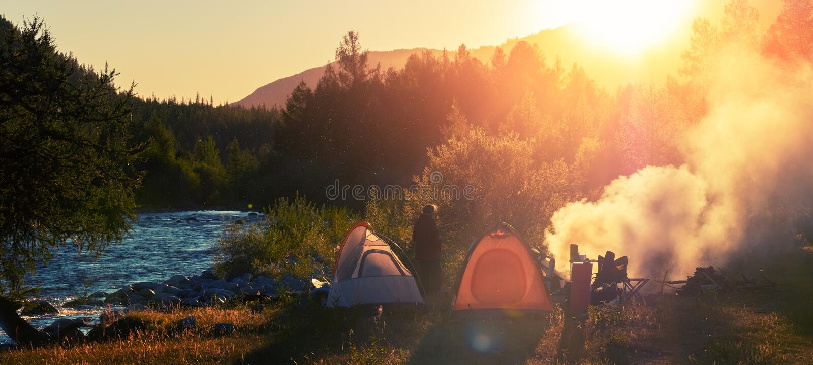 Panorama of the camp in the wild area. Hikers set the tents near the river and make fire at sunset royalty free stock photo
