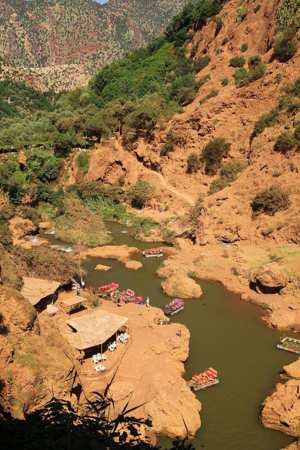 Panorama in canion met rivier, naaldboombomen en rood die berggezicht met groene installaties wordt gestippeld - Ourika-Vallei, stock foto's