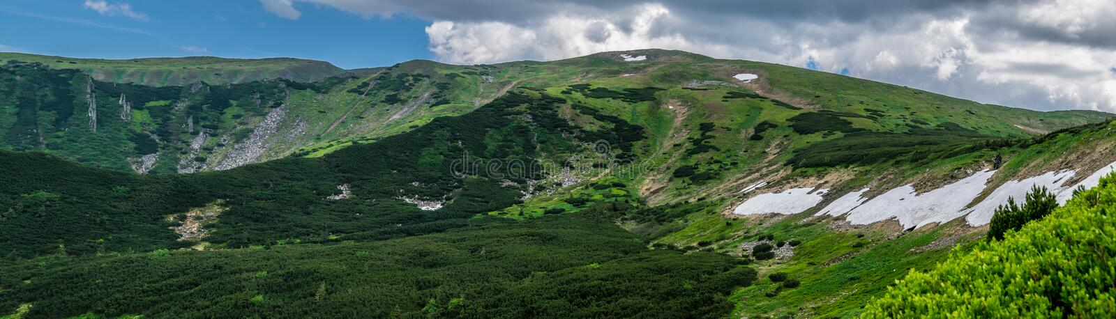 Panorama of Carpathian mountains landscape. Panorama of Carpathian mountain range in Ukraine. Snow on shaded mountainside. Carpathian National Nature Park in royalty free stock photography