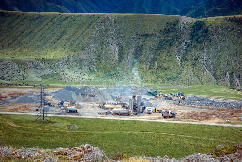 Panorama of cement factory in Altai green hills backgrounds. Manufacturing site between the mountain. Industrial landscape stock photography