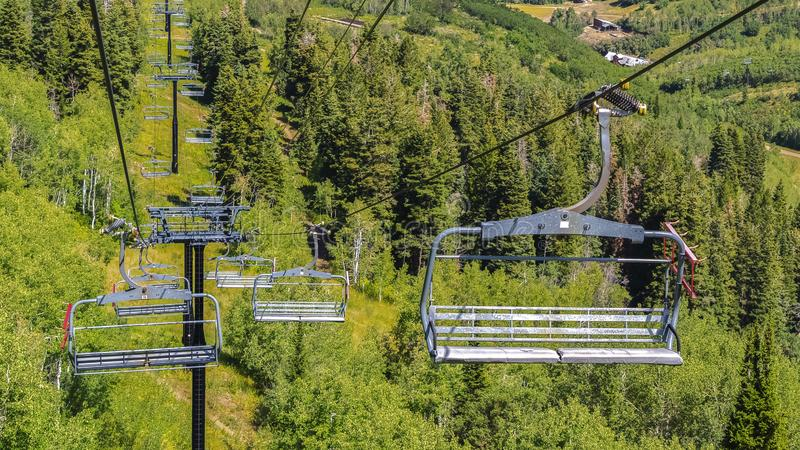 Panorama Chairlifts against green trees and mountain with hiking trails at off season. Aerial view of the ski resort in Park City, Utah with buildings on a stock images