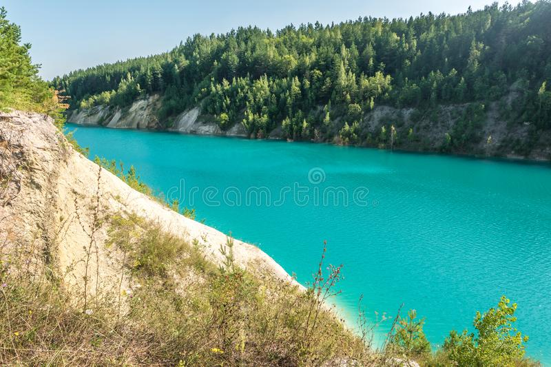 Panorama of chalkpit on limestone coast of huge turquoise lake or river near forest. Chalk quarry filled with water.  royalty free stock photography