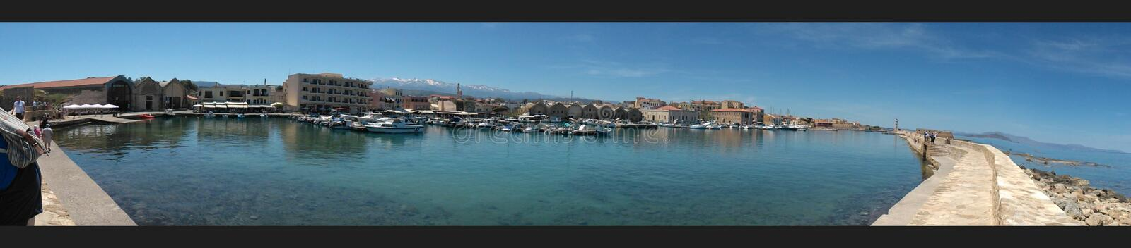 Panorama Chania Harbour, Greece. A panoramic view of Chania harbour in Crete with boats, ancient buildings and mountains in the distance on a sunny day with stock photos