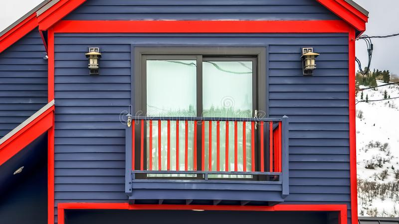 Panorama Close up of home exterior with vibrant blue wall red frames and small balcony. Cloudy sky and mountain covered with snow in winter cna be seen in the stock photo
