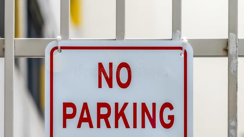 Panorama Close up of No Parking sign on awhite metal gate with building in the background royalty free stock image