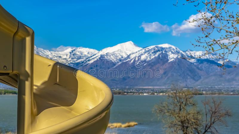 Panorama Close up of a spiral slide at a sunny playground with view of a lake. A mountain with snowy peaks against rich blue sky cna be seen in the distance stock photos