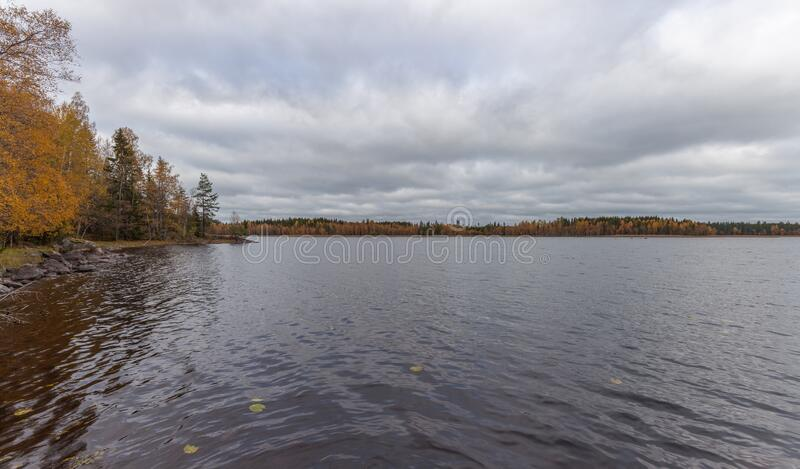 Panorama with cloudy sky over pier on the lake. Autumn forest in the background, Sweden, selective focus. Panorama with cloudy sky over the pier on the lake royalty free stock photography