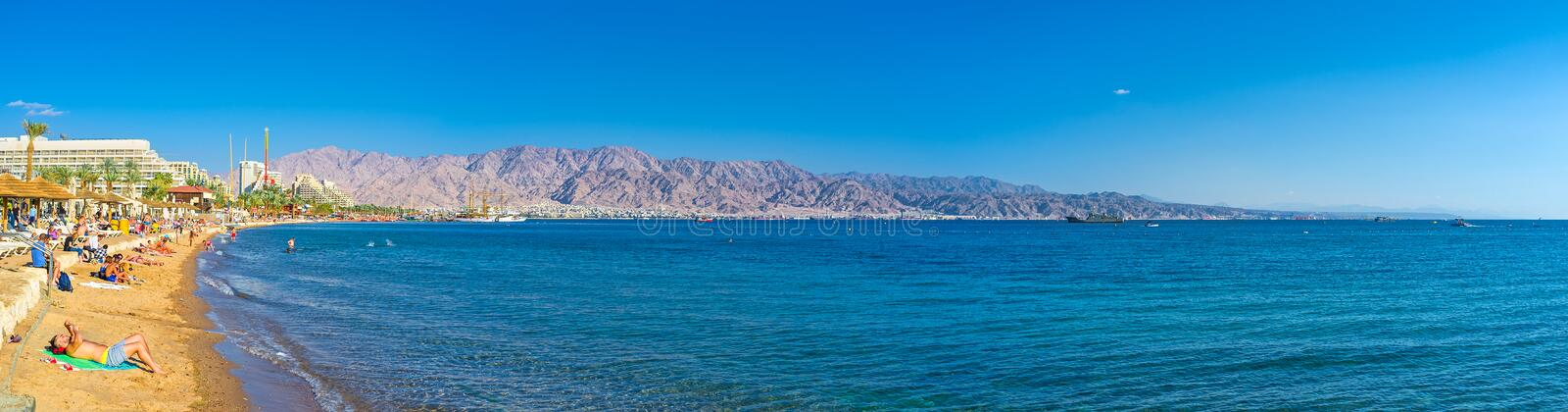 Panorama of the coast of Eilat. EILAT, ISRAEL - FEBRUARY 23, 2016: The scenic coastline with the comfortable sand beach and picturesque rocky mountains of Aqaba royalty free stock photography