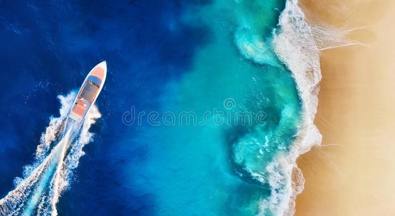 Panorama of a coast and fast boat as a background from top view. Aerial view of luxury floating boat. Nusa Penida island, Indone royalty free stock photos