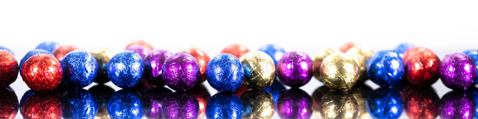 Panorama with colorful chocolate balls in front of white background royalty free stock images