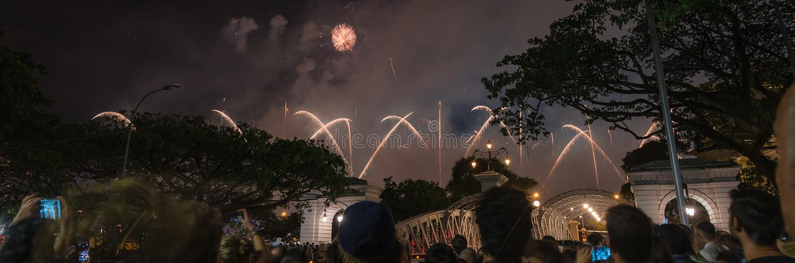 Panoramic firework display celebrating New Year party with blurry people watching in Singapore royalty free stock image