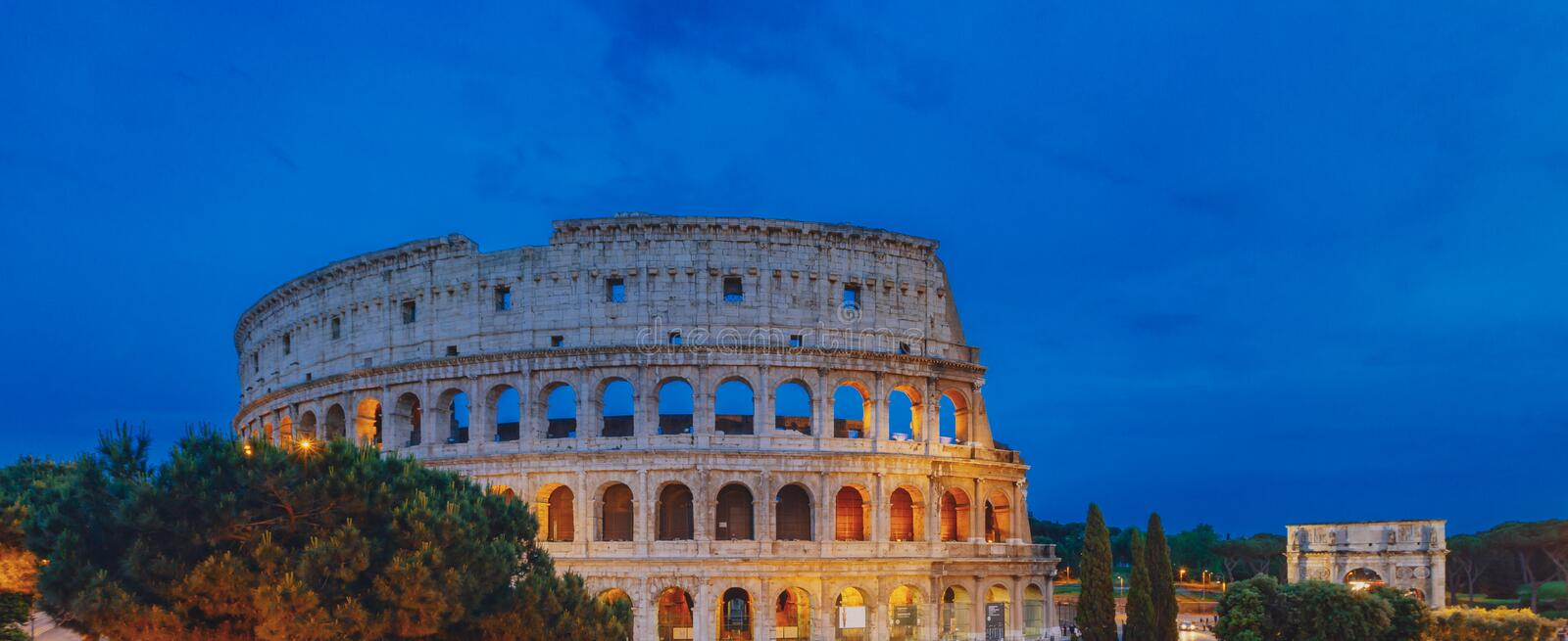 Panorama of Colosseum and Arch of Constantine under blue sky at dusk in Rome, Italy royalty free stock photo