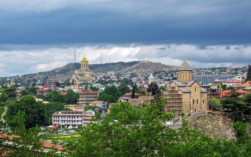Panorama com a catedral da trindade santamente de Tbilisi e de igreja do Virgin do St de Metekhi da fortaleza antiga de Narikala, fotos de stock