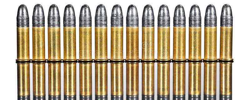 Panorama com fileira dos cartuchos ou da munição contra a parte traseira branca foto de stock