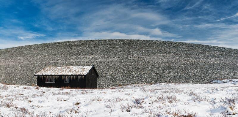 Panorama con la cabina di legno norvegese tradizionale accanto alla collina delle rocce immagine stock libera da diritti