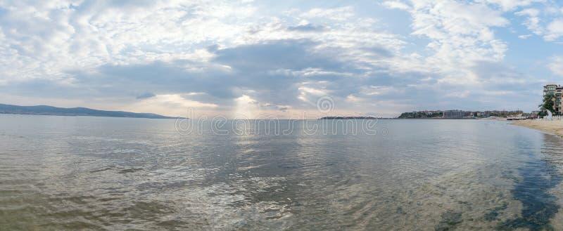 Panorama con los rayos de sol o los rayos del sol que miran a escondidas a través de las nubes en una salida del sol en la playa  imagenes de archivo