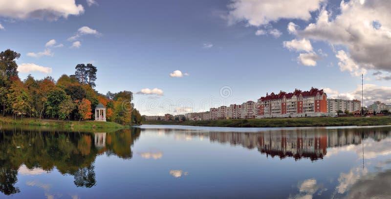 Panorama con uno stagno, una città e l'autunno fotografie stock