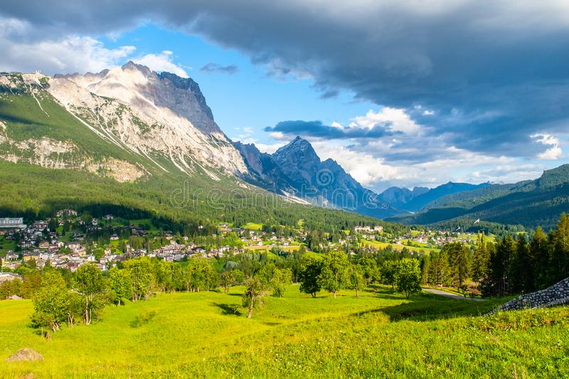 Panorama of Cortina d`Ampezzo with green meadows and alpine peaks on the background. Dolomites, Italy. stock photo