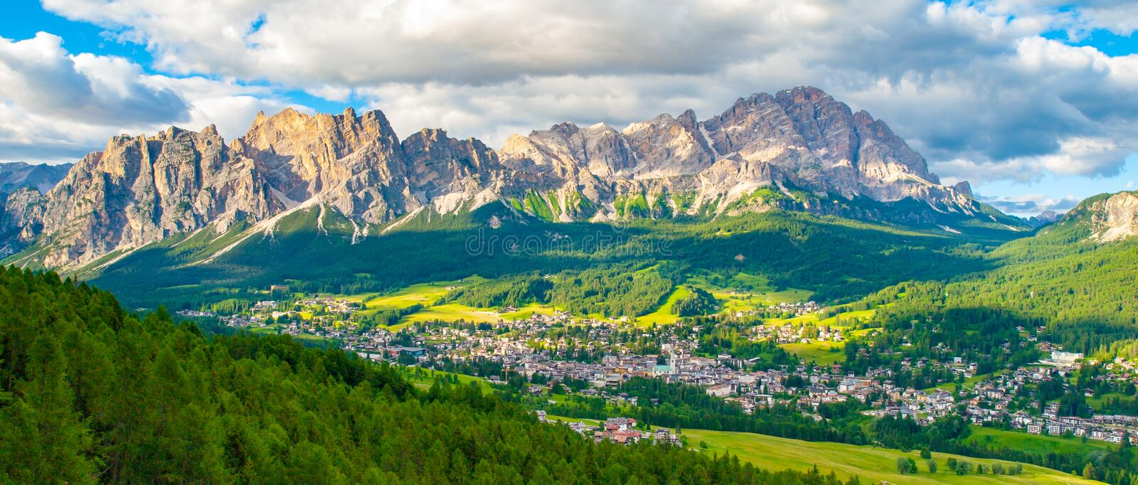 Panorama of Cortina d`Ampezzo with green meadows and alpine peaks on the background. Dolomites, Italy. royalty free stock photography