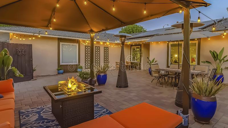 Panorama Cozy brick patio of a home with colorful seating area under a pavilion. A dining area under an umbrella can be seen near the house and brown wooden stock images