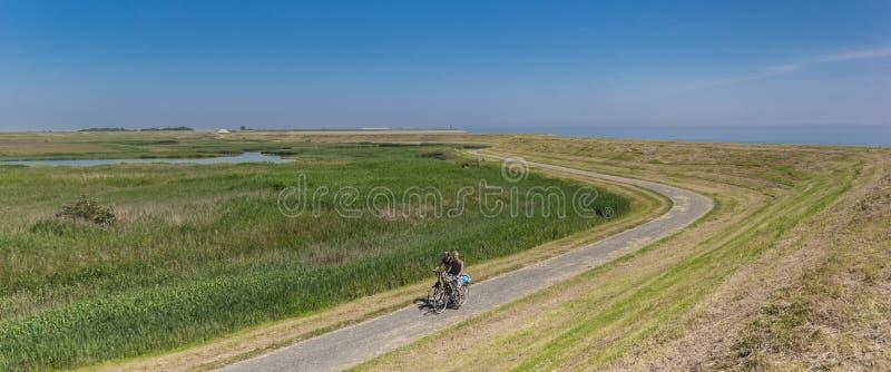 Panorama d'un couple sur des bicyclettes le long d'une digue sur l'île de Texel photo stock