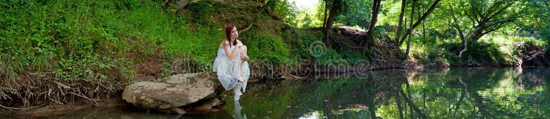 Panorama d'une mariée triste s'asseyant sur une roche photo stock
