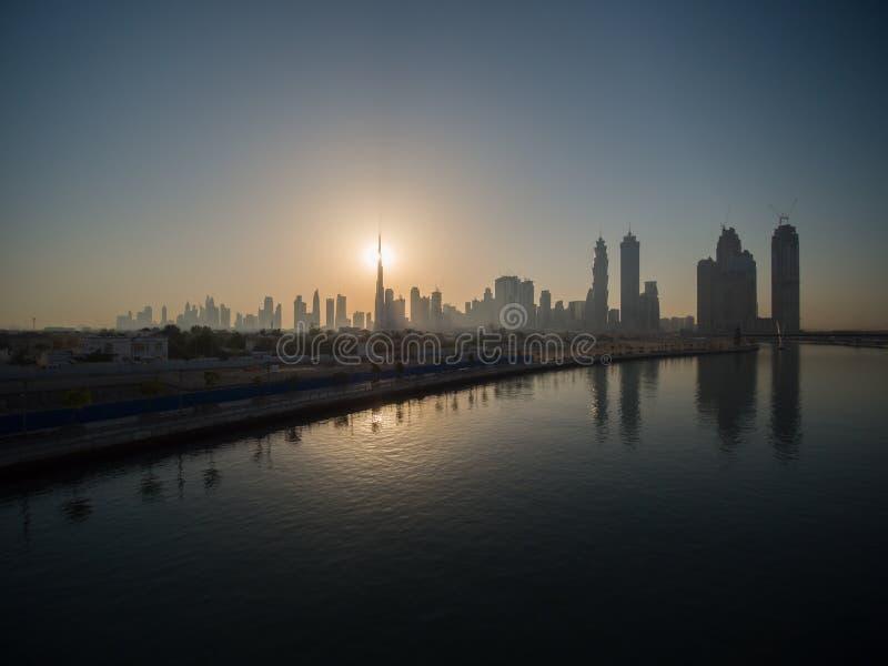 Panorama da cidade de Dubai cedo na manhã no nascer do sol com uma ponte sobre o canal Dubai da cidade grego fotos de stock