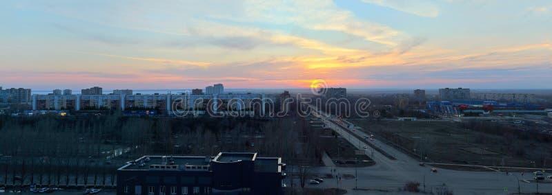 Panorama da cidade que negligencia a interseção de ruas de Yubileinaya e de Frunze contra o céu e as nuvens do por do sol imagens de stock